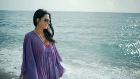 Mujer romántica hermosa que camina en la playa en vacaciones de verano almacen de video