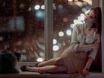Mujer romántica y un gato que se sienta en una ventana Imágenes de archivo libres de regalías