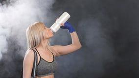 Mujer rubia activa en sportwear que bebe una coctelera de la proteína y que se coloca en el gimnasio después de entrenamiento Se  almacen de metraje de vídeo