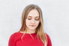Mujer rubia adorable en el vestido rojo que mira cuidadosamente abajo del pensamiento sobre sus relaciones con el novio que tiene Imagenes de archivo