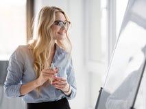 Mujer rubia alegre que escribe su idea en un flipchart foto de archivo