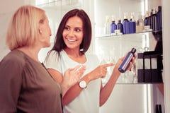Mujer rubia alegre que habla con el consultor de belleza imagen de archivo libre de regalías