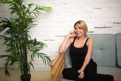 Mujer rubia alegre que habla en el teléfono móvil mientras que se sienta en el sofá cómodo cerca de la planta verde Foto de archivo libre de regalías