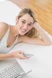 Mujer rubia alegre que miente en su cama usando su smartphone Foto de archivo