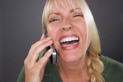 Mujer rubia alegre que usa el teléfono celular Foto de archivo