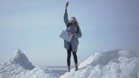 Mujer rubia atractiva con el mapa que intenta coger situación del teléfono móvil de la tenencia de la red la alta en el bloque de almacen de metraje de vídeo