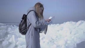 Mujer rubia atractiva con la mochila que comprueba el mapa delante del hielo en el del norte o South Pole Viajes turísticos en metrajes