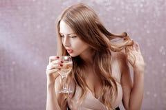 Mujer rubia atractiva con un vidrio de champán en el partido Fotos de archivo libres de regalías