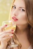 Mujer rubia atractiva con un vidrio de champán en el partido Imágenes de archivo libres de regalías