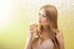 Mujer rubia atractiva con un vidrio de champán en el partido Foto de archivo libre de regalías
