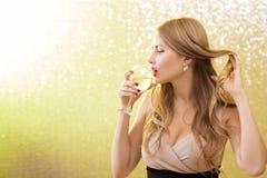 Mujer rubia atractiva con un vidrio de champán en el partido Fotografía de archivo libre de regalías