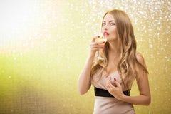Mujer rubia atractiva con un vidrio de champán en el partido Imagen de archivo