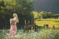 Mujer rubia atractiva de la señora de los ojos azules en vestido airoso rosado en el prado de la manzanilla de la margarita que s Imágenes de archivo libres de regalías