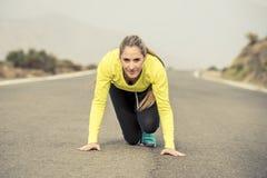 Mujer rubia atractiva del deporte lista para comenzar a correr la carrera del entrenamiento de la práctica que comienza en paisaj Imagen de archivo libre de regalías