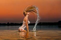 Mujer rubia atractiva en agua en la puesta del sol Fotografía de archivo