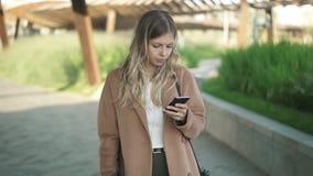 Mujer rubia atractiva en capa que camina y que mira su smartphone en otoño