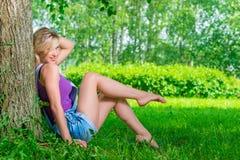 Mujer rubia atractiva en el parque en un día de verano Imagenes de archivo