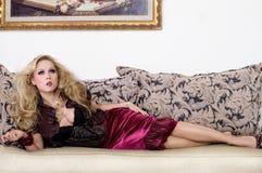 Mujer rubia atractiva en el sofá Imágenes de archivo libres de regalías