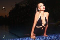 Mujer rubia atractiva en el traje de baño que presenta en piscina Foto de archivo libre de regalías