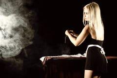 Mujer rubia atractiva en el traje del ama de casa, camisa blanca que plancha con hierro viejo estilo retro en un fondo oscuro Fotografía de archivo libre de regalías