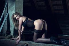 Mujer rubia atractiva en ropa interior negra que se arrodilla en la madera Imágenes de archivo libres de regalías