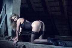 Mujer rubia atractiva en ropa interior negra que se arrodilla en la noche Imagen de archivo libre de regalías