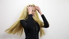 Mujer rubia atractiva hermosa en actitud negra del vestido contra fondo del estudio Cantidad de la cámara lenta almacen de video