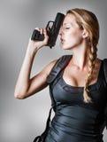 Mujer rubia atractiva joven con la arma de mano Foto de archivo