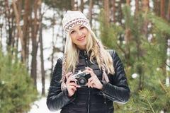 Mujer rubia atractiva joven con una cámara vieja Fotos de archivo libres de regalías
