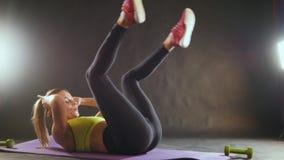 Mujer rubia atractiva joven que ejercita - entrenamiento para abdominal metrajes