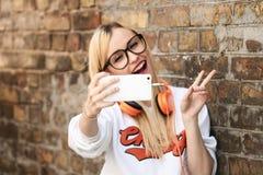 Mujer rubia atractiva joven que hace la foto del selfie en smartphone fotos de archivo