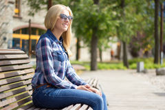 Mujer rubia atractiva joven que se sienta en parque Imágenes de archivo libres de regalías