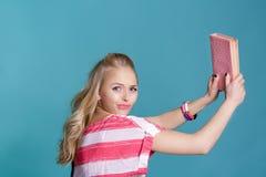 Mujer rubia atractiva joven que sostiene el libro rosado en fondo azul Fotos de archivo libres de regalías