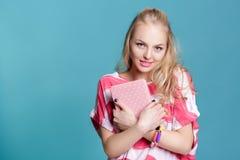 Mujer rubia atractiva joven que sostiene el libro rosado en fondo azul Fotografía de archivo libre de regalías
