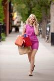 Mujer rubia atractiva que camina abajo de la calle Imágenes de archivo libres de regalías