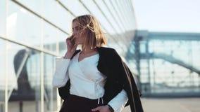 Mujer rubia atractiva que camina cerca del centro de negocios y que habla en el teléfono Mirada elegante, blusa blanca elegante almacen de video
