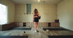 Mujer rubia atractiva que camina derecho a través del estudio de la yoga la que sostiene su estera del deporte muy feliz y que go almacen de video