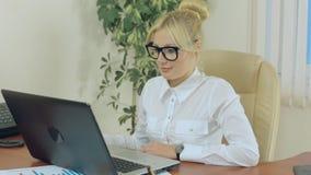 Mujer rubia atractiva que mira el monitor almacen de metraje de vídeo