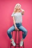 Mujer rubia atractiva que presenta en la silla Imágenes de archivo libres de regalías