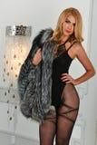 Mujer rubia atractiva que presenta en un interior que lleva la ropa interior y el abrigo de pieles sensuales Imagen de archivo libre de regalías
