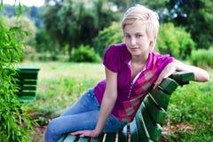 Mujer rubia atractiva que se sienta en banco en parque Fotografía de archivo libre de regalías