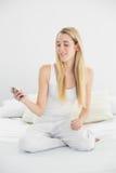 Mujer rubia atractiva que se sienta en su cama que lleva a cabo su smartphon Imagen de archivo libre de regalías