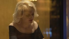 Mujer rubia atractiva que se sienta solamente en la tabla de la barra, buscando al hombre, coqueto almacen de video