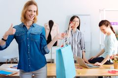 Mujer rubia atractiva que sostiene la bolsa de papel azul imágenes de archivo libres de regalías