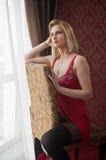 Mujer rubia atractiva y atractiva con ropa interior roja de la muñeca y medias negras que plantean sentarse en silla cerca de una Fotos de archivo