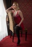 Mujer rubia atractiva y atractiva con ropa interior roja de la muñeca y medias negras que plantean sentarse en silla cerca de una Foto de archivo