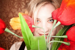 Mujer rubia bastante joven con las flores plásticas Imagen de archivo
