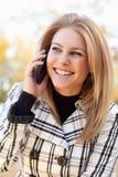 Mujer rubia bastante joven en el teléfono afuera Imágenes de archivo libres de regalías