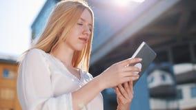 Mujer rubia bastante joven que usa el dispositivo de la tableta afuera en la calle Sonrisa de la mujer, golpeando ligeramente en  metrajes