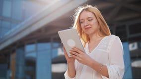 Mujer rubia bastante joven que usa el dispositivo de la tableta afuera en la calle Sonrisa de la mujer, golpeando ligeramente en  almacen de metraje de vídeo